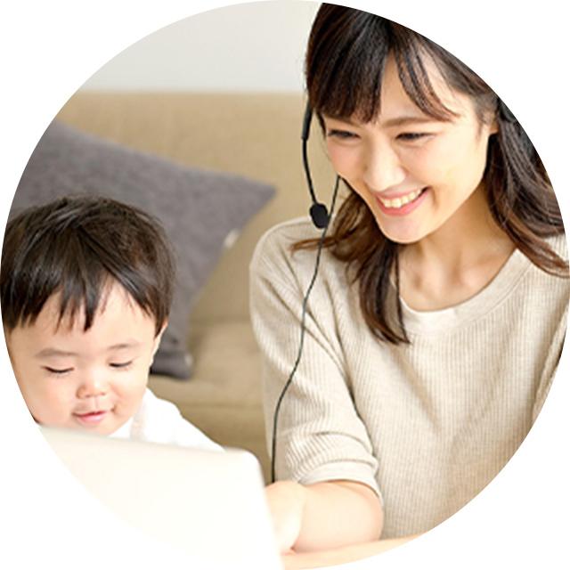 赤ちゃんと一緒にオンライン授業を受けている女性の写真