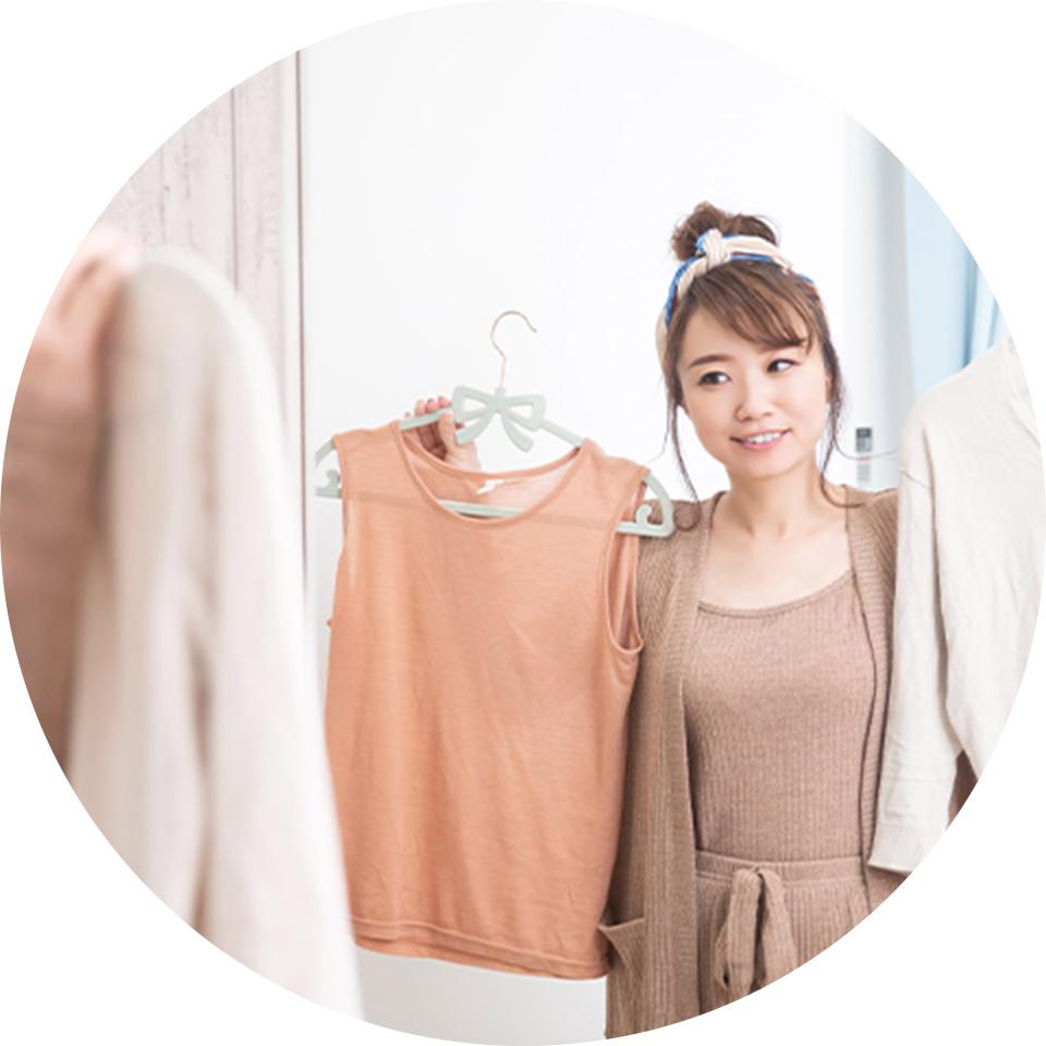 鏡の前で服を選んでいる女性の写真