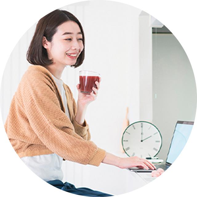 飲みものを片手にオンライン授業を受けている女性の写真